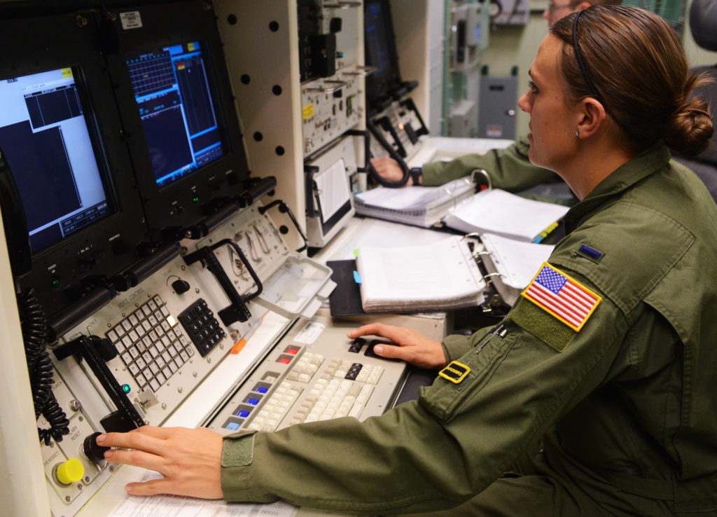 A combat missile crew commander using the trackball of the REACT console