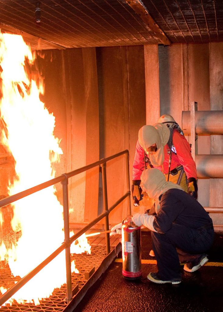 Instructor instructs a damage control student in the Trident Training Facility fire trainer at Naval Submarine Base Kings Bay.