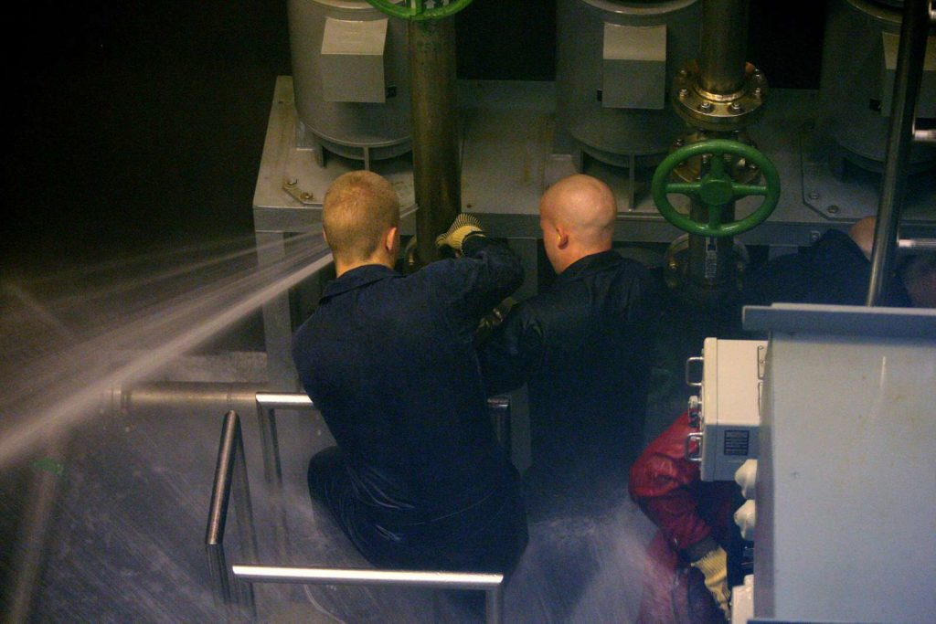 A team of midshipmen works to patch a ruptured pipe in the Trident Training Facility damage control wet trainer